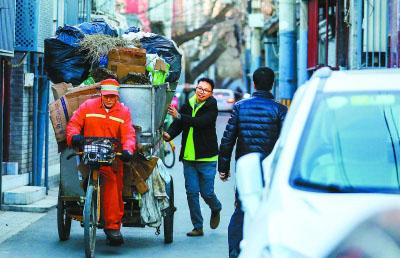"""周末一大早,刘涛看环卫师傅的垃圾清运车从远处驶来,赶忙跑过去""""护送""""小车走出胡同。"""