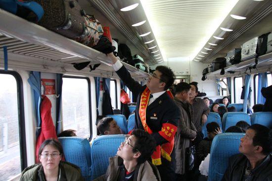 王冠雄正在巡视整理车厢行李架